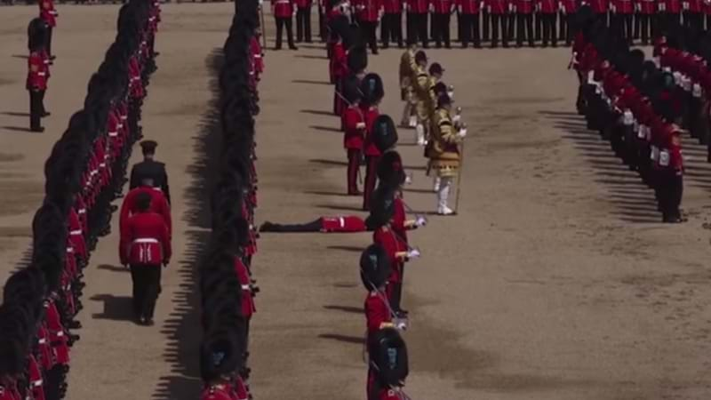 Article heading image for Watch As Royal Guards Remain Completely Still After Fellow Guard Drops Unconscious